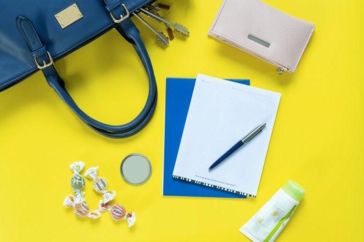 block notes su sfondo giallo e accessori che escono da una borsa femminile blu