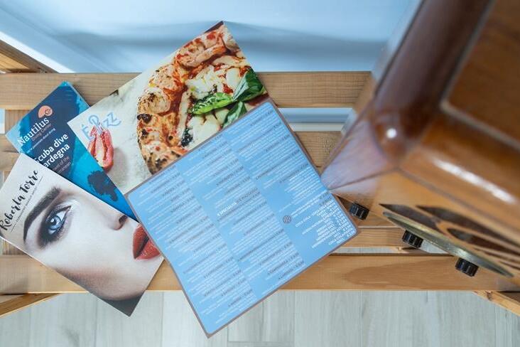 brochure a tre ante con menu pizzeria aperto su mensola di legno