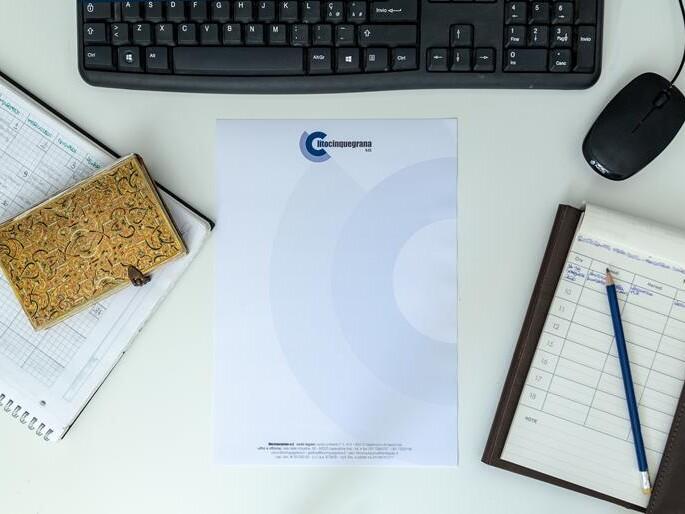 carta intestata litocinquegrana su scrivania con tastiera pc e block notes ai lati