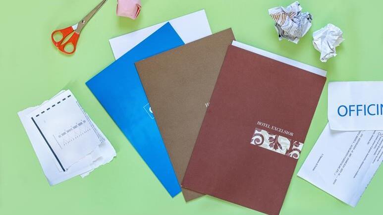 cartelline porta documenti su tavolo verde e carta appallottolata da buttare