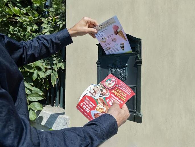 mani maschili che mettono dei volantini A5 nella cassetta delle lettere