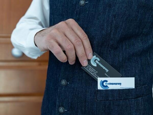 mano maschile che mette in tasca un biglietto da visita litocinquegrana