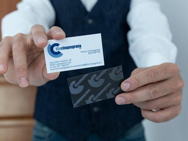 mano maschile che tiene tra le mani due biglietti da visita litocinquegrana