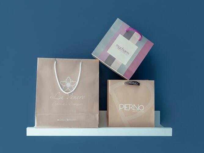 tre tipi di shopper di carta litocinquegrana su mensola bianca con sfondo blu