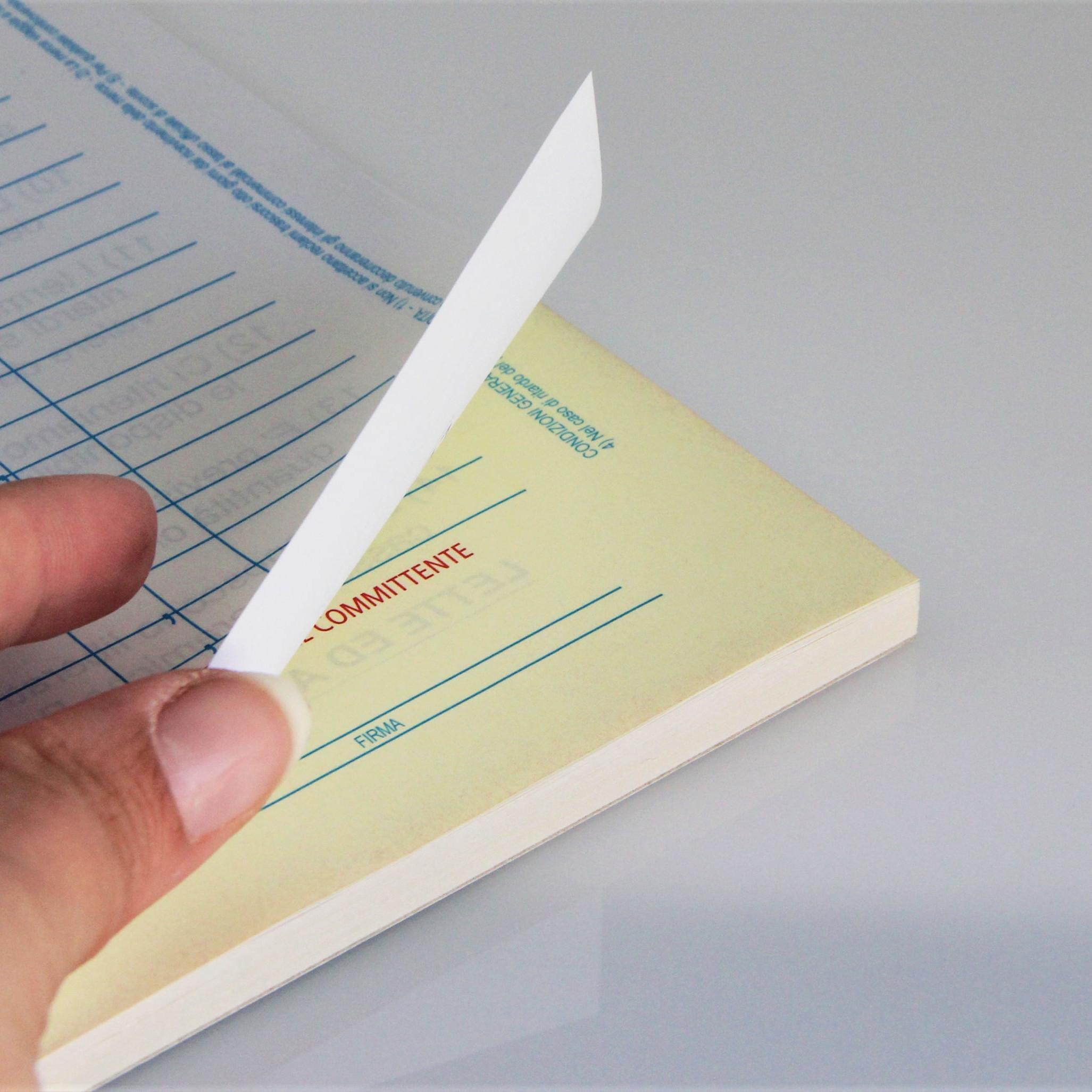 dettaglio blocco copiativo con mano che sfoglia i fogli