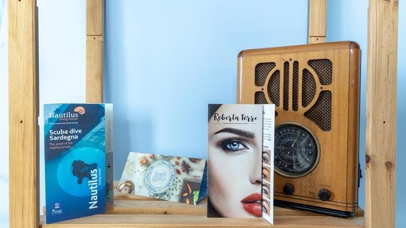 brochure appoggiate su di una mensola di legno con accanto una radio vintage