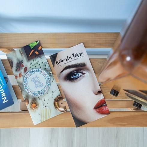 brochure appoggiate su di una mensola di legno