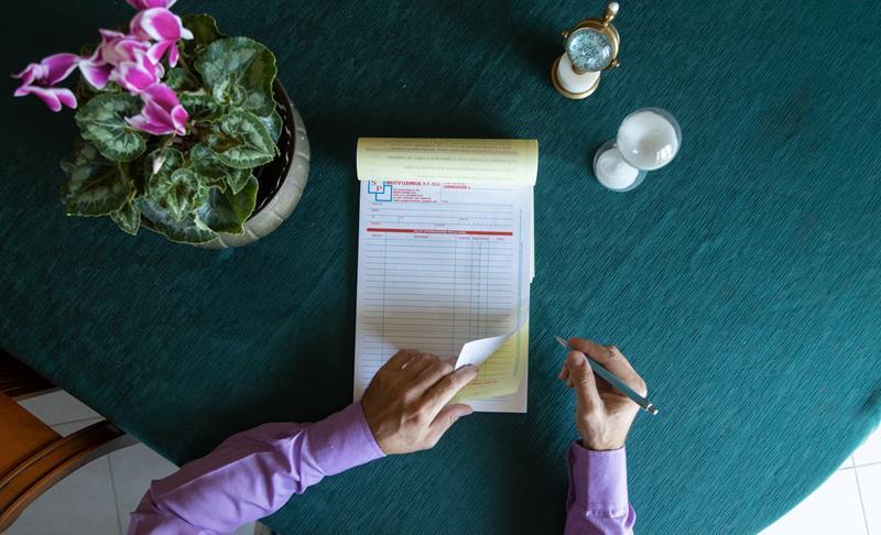 mano maschili che scrivono su un blocco copiativo su tavolo verde