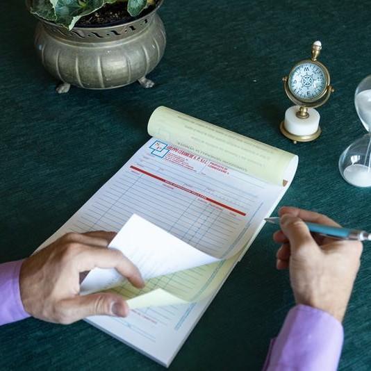 mano maschili che scrivono su un blocco copiativo appoggiato su un tavolo verde scuro