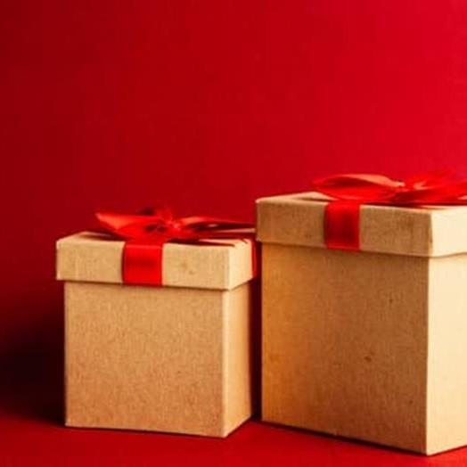 scatola beigee con fiocco rosso e sfondo rosso