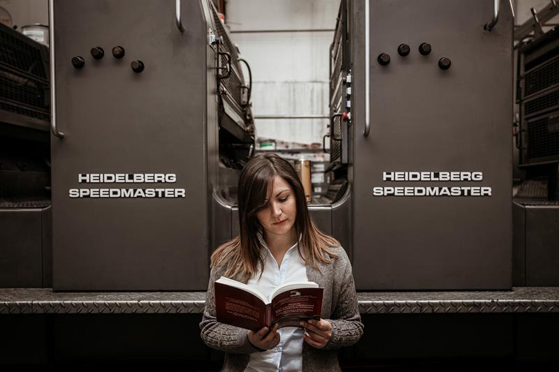 donna che legge un libro con heidelberg speedmaster alle sue spalle