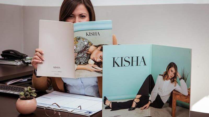 donna che sorride coprendosi bocca e naso con un catalogo di moda seduta ad una scrivania