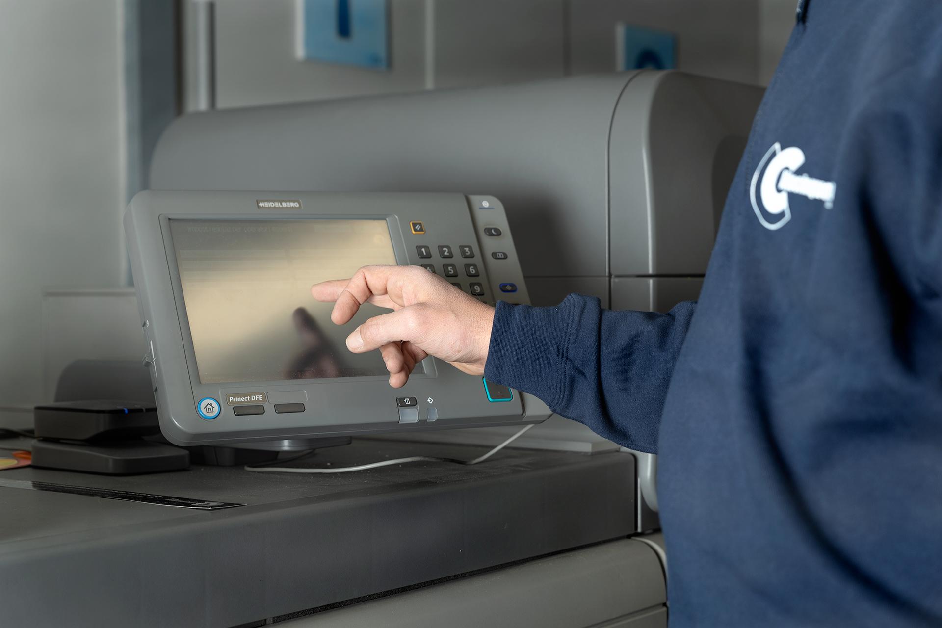 mano maschile che mette in funzione una stampante digitale heidelberg versafire