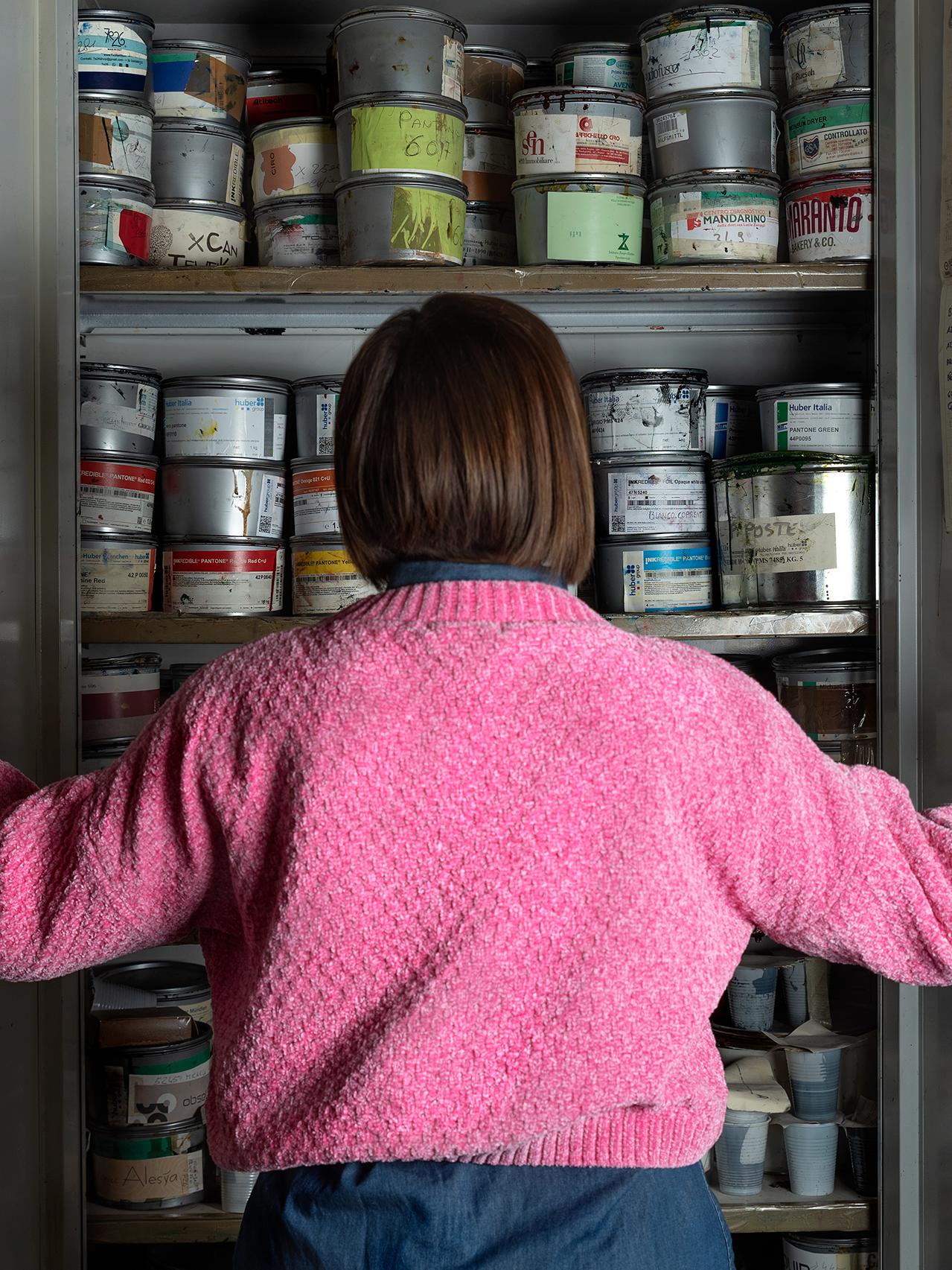 donna di spalle con maglione rosa che apre una armadio pieno di inchiostri per la stampa offset