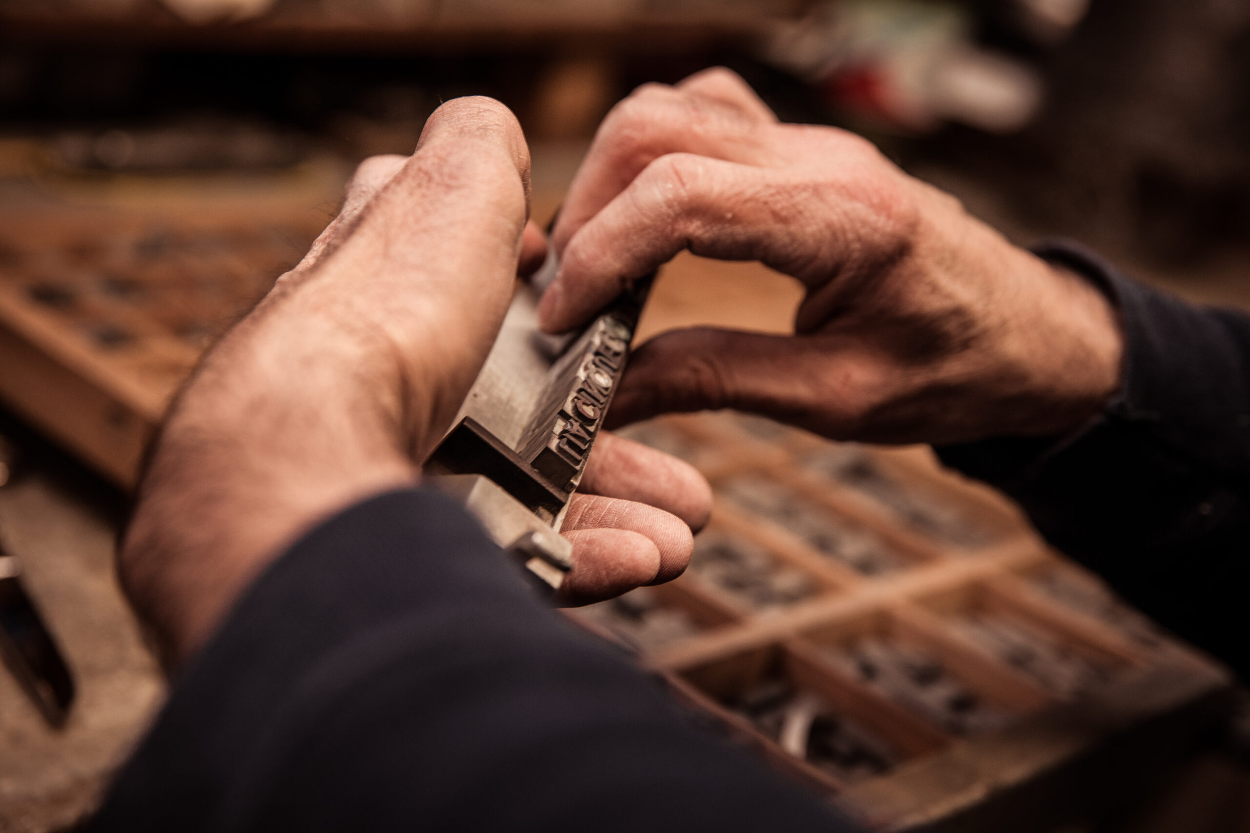 mani maschili che compongono una parola con i caratteri mobili in piombo