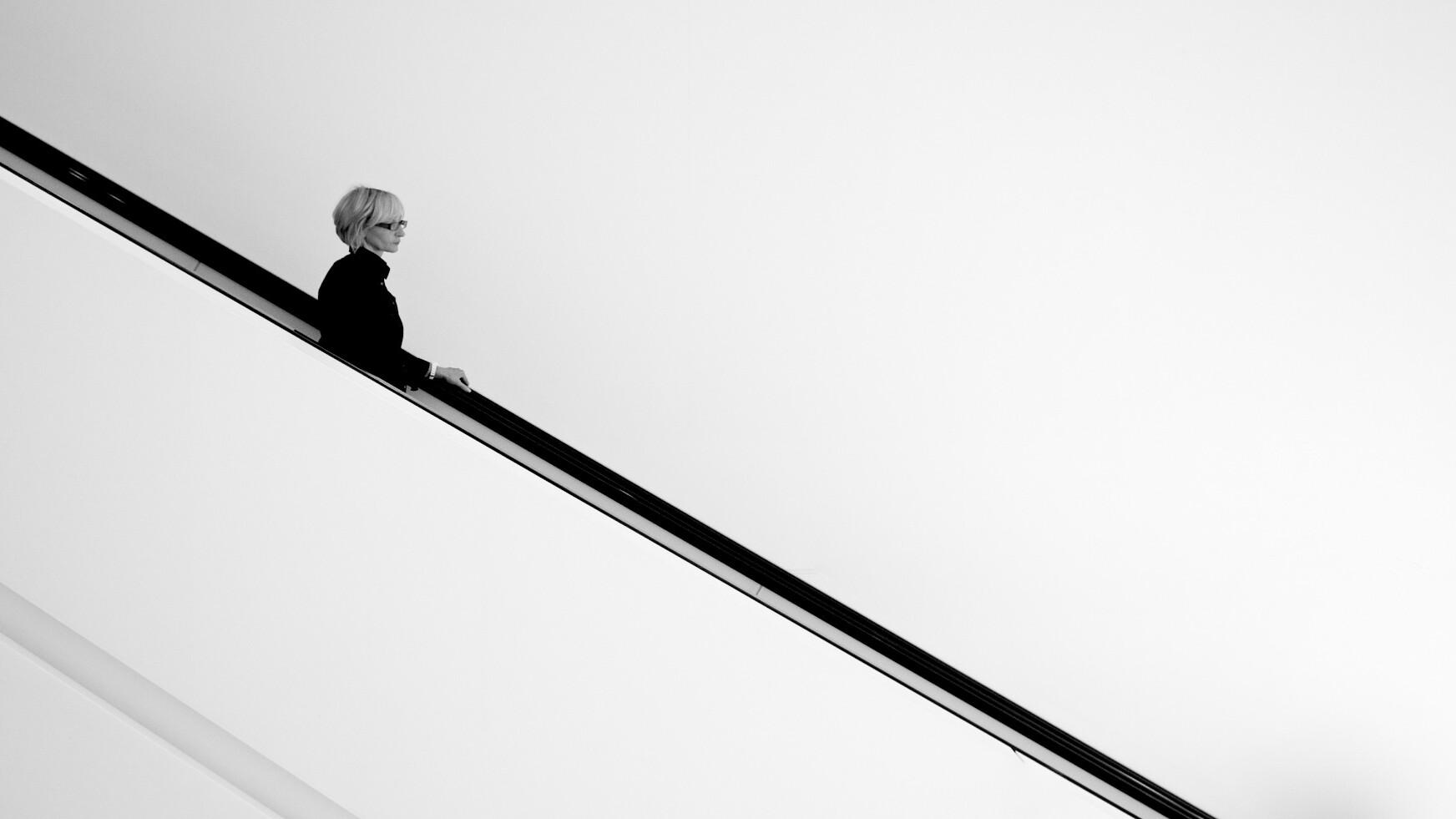 spazio vuoto nella fotografia, donna con occhiali su scale nerel
